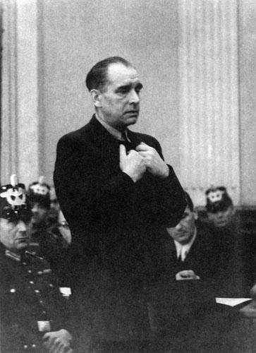 Julius Leber steht mit den Händen am Revers vor dem Gericht. Im Hintergrund Wachen.