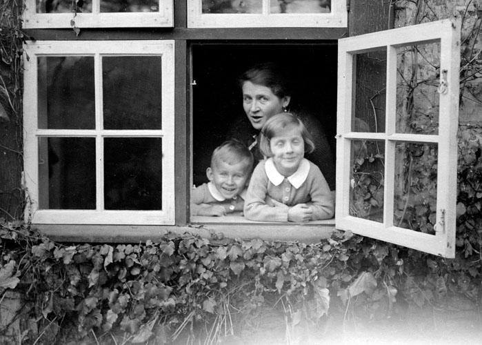 Annedore mit Kindern im Fenster ihres Hauses