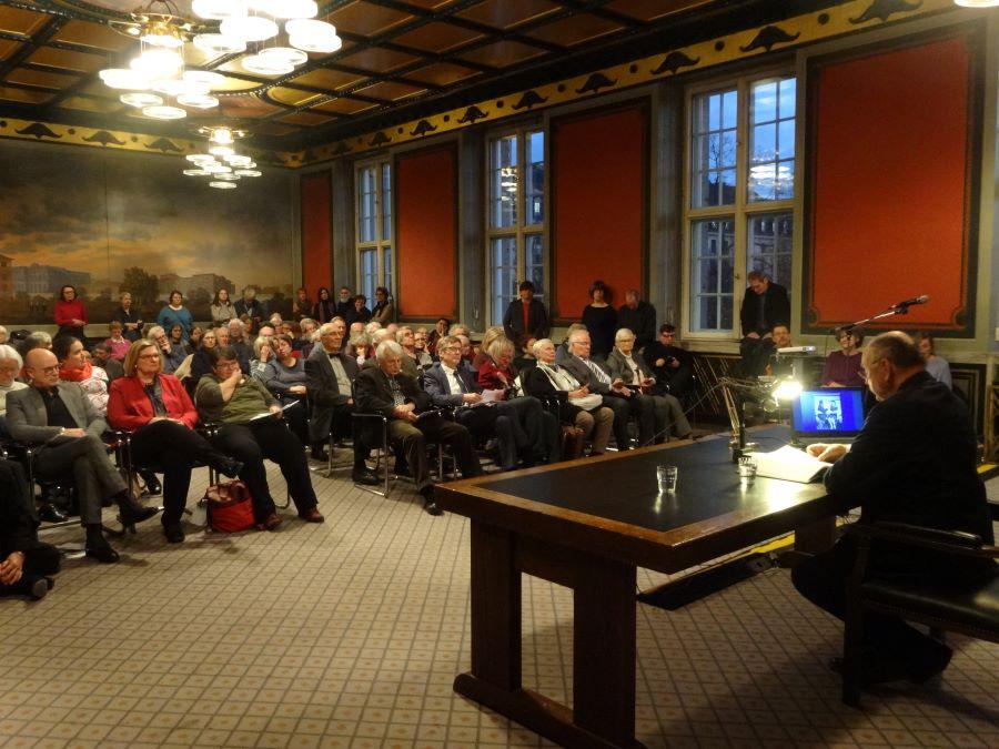 Referent am Schreibtsch mit Blick auf Publikum