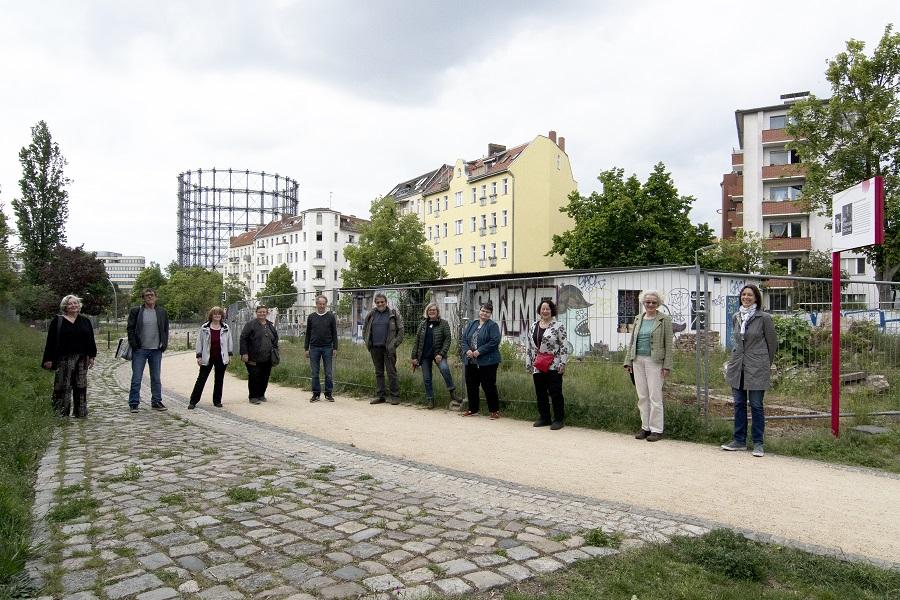 11 Menschen stehen vor der ehemaligen Kohlenhandlung, im Hintergrund der Gasometer Schöneberg