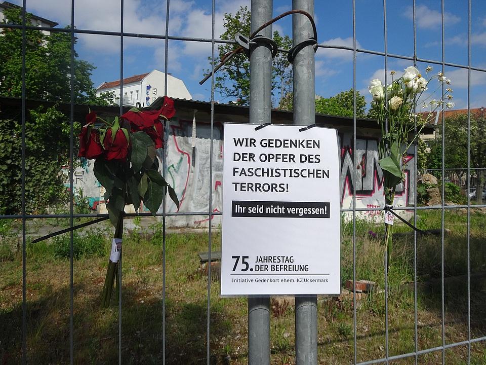 Rosen und Plakat am Zaun
