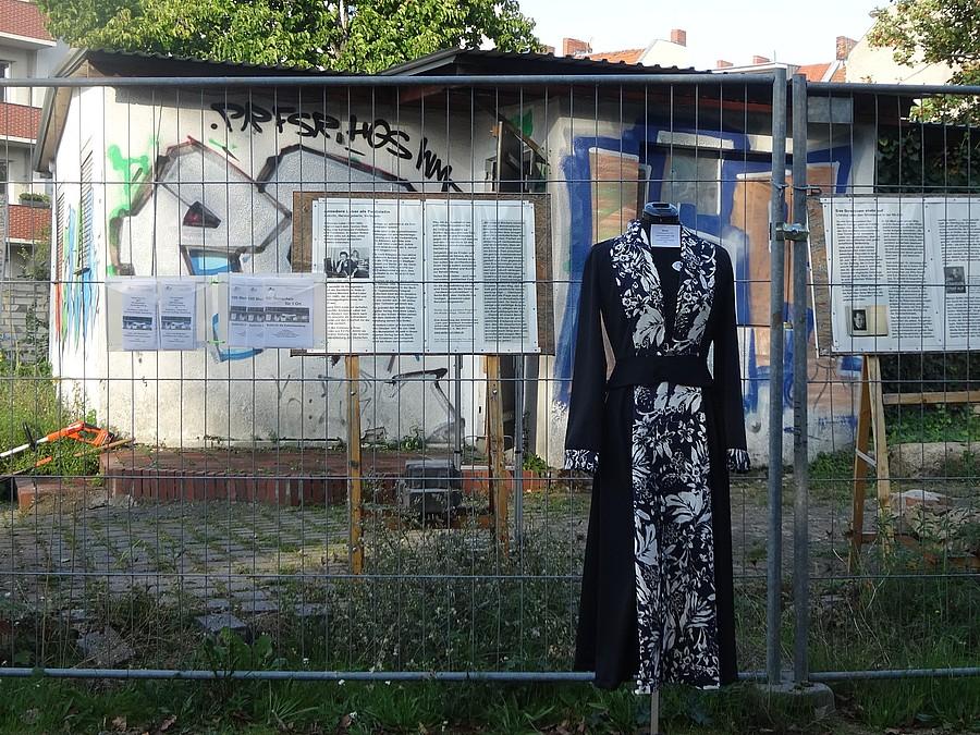 Mantelkleid auf Schneiderpuppe vor dem Zaun der Kohlenhandlung
